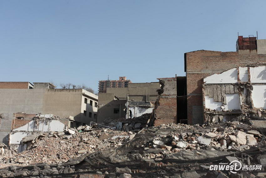 照片右边没有拆的房子里还住着4户人家,左侧废墟下就是他们进出的通道