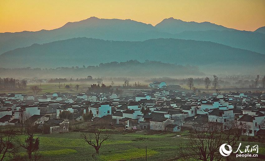 """黟县卢村的清晨美景,云雾缭绕,徽派民居在油菜花海间错落有致。黟县是""""徽商""""和""""徽文化""""的发祥地之一,也是安徽省省级历史文化名城。境内存有大量的明清民居、祠堂、牌坊、园林,更有世界文化遗产西递、宏村古村落,黟县又被称为""""中国画里乡村""""、""""桃花源里人家""""。"""