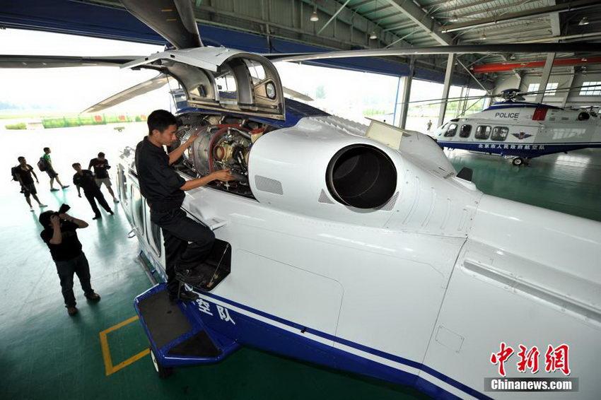 图为机修技师检查飞机发动机