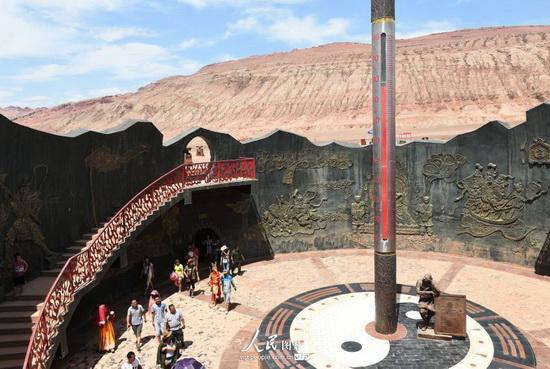 7月13日,游客在新疆吐鲁番火焰山景区游览,巨型金箍棒造型温度计显示