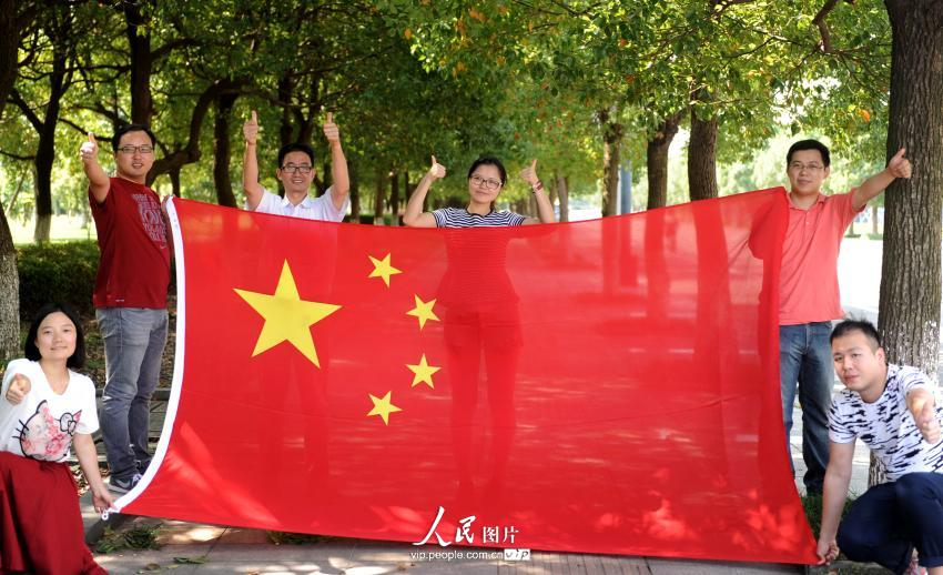 2014年9月28日,浙江宁波市北仑百姓与国旗合影为祖国点赞,喜迎新中国图片