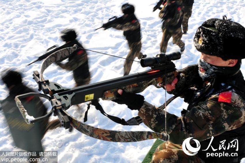 12月24日,新疆公安边防总队训练基地女子特勤分队正在进行小组战术训练,一名女队员使用警用弓弩占领制高点。