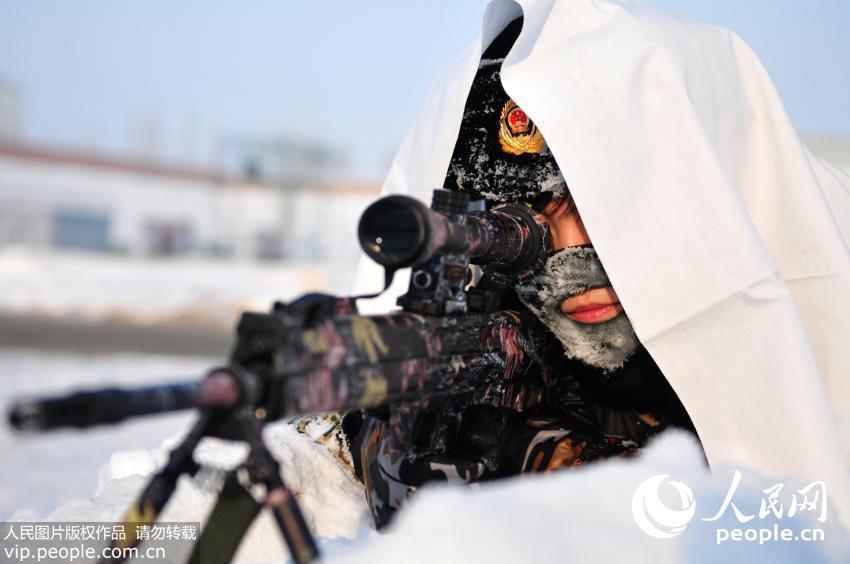 12月24日,新疆公安边防总队训练基地女子特勤分队狙击手王琼宇正在进行雪地伪装潜伏狙击训练。