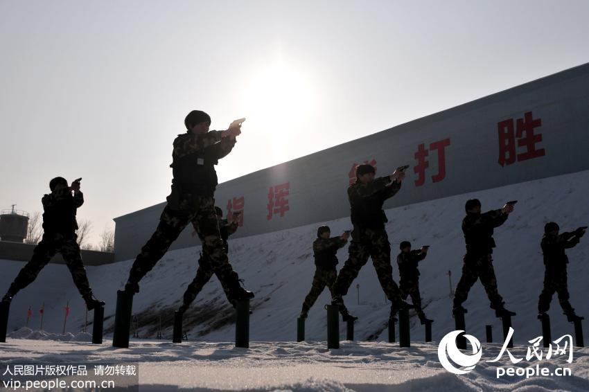 12月24日,新疆公安边防总队训练基地女子特勤分队队员站在桩子上进行手枪狙枪平衡训练。