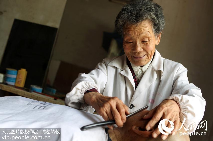 4月21日,80岁的蔡瑞云老人在为顾客刮脸。