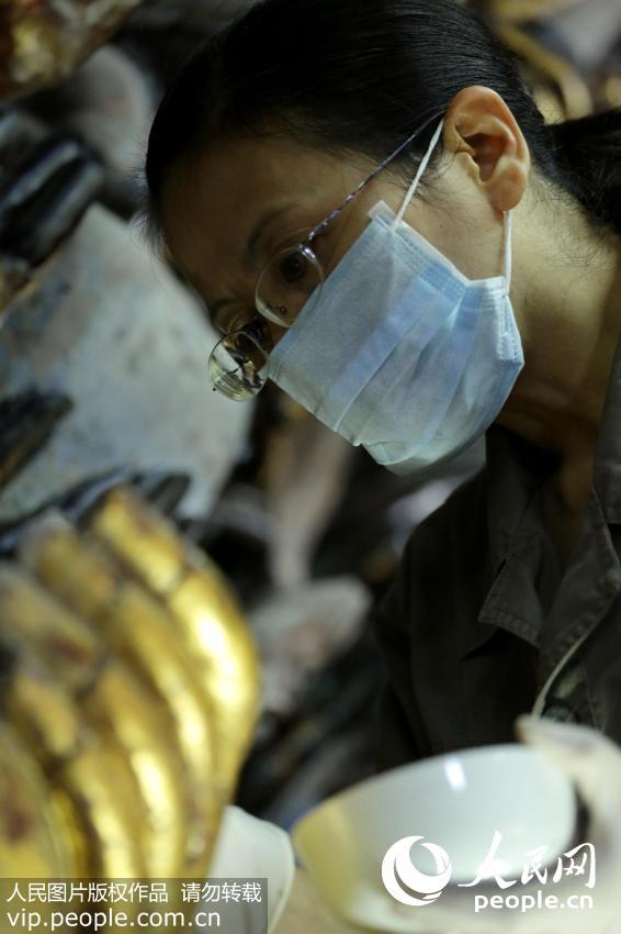 2014年10月8日,千手观音抢救性保护工程现场,陈卉丽正在进行石质修复。