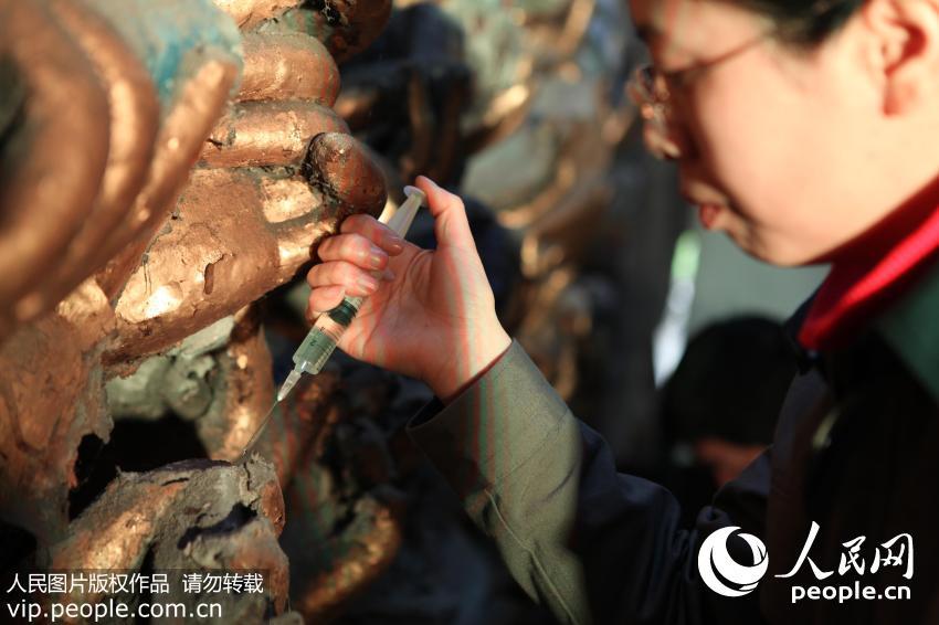 """2011年4月17日,千手观音抢救性保护工程现场,石质修复师陈卉丽在对风化疏松的岩体""""打针"""",注射固化剂进行加固。"""