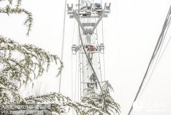 2016年11月22日,江苏丰县供电公司电建二公司施工人员冒雪在常于线110千伏高压输电塔架线施工作业。 当日,丰县迎来入冬的第一场中雪,最低气温降至零下3摄氏度,国网丰县供电公司采取应急预案,加快线路升级改造,确保供电迎峰度冬。(高荣光/人民图片) (声明:凡带有人民图片字样图片,系版权图片,受法律保护,使用(含转载)需付费,欢迎致电购买:010-65363647或021-63519288。)