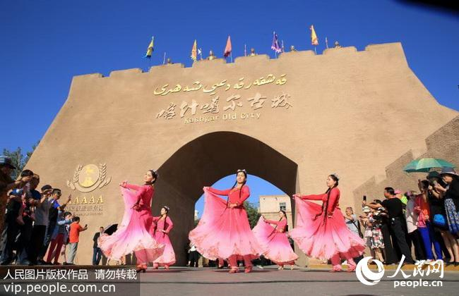 2017年6月19日,在新疆喀什噶尔古城景区举行的入城仪式上,维吾尔族同胞在为游客表演民族舞蹈。 国家5A级景区喀什噶尔古城距今已有2100多年历史,自去年5月1日以来,景区每天上午都举行具有浓郁民族风情的入城仪式,欢迎游客的到来。(柴更利/人民图片) (声明:凡带有人民图片字样图片,系版权图片,受法律保护,使用(含转载)需付费,欢迎致电购买:010-65363647或021-63519288。)