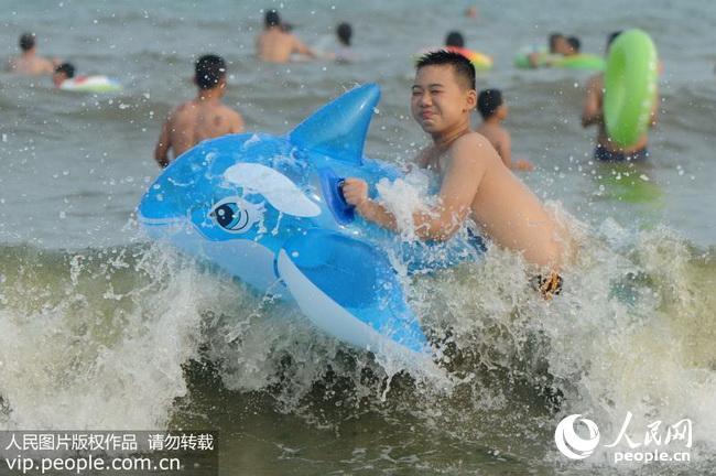 2017年7月10日,新一轮高温来袭,山东省青岛市海水浴场迎来众多下海纳凉的游客。各种泳具花花绿绿点缀海滩,成为夏天一道别样的风景。 根据最新气象预报,未来10天,中国中东部地区将迎来今年来范围最广、强度最强高温天气,最强时段,预计全国高温面积可达364万平方公里,将覆盖21个省份。(王海滨/人民图片) (声明:凡带有人民图片字样图片,系版权图片,受法律保护,使用(含转载)需付费,欢迎致电购买:010-65368384或021-63519288。)