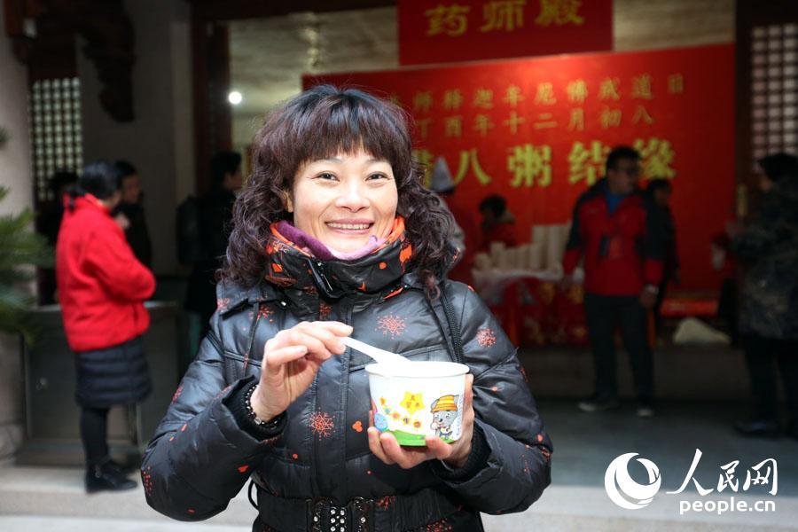 市民展示刚领取到的腊八粥。