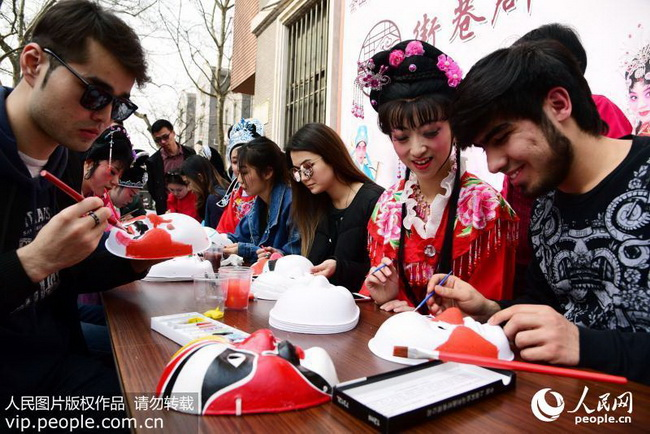 2018年3月25日,外国留学生正在与戏曲票友一起画戏曲脸谱。