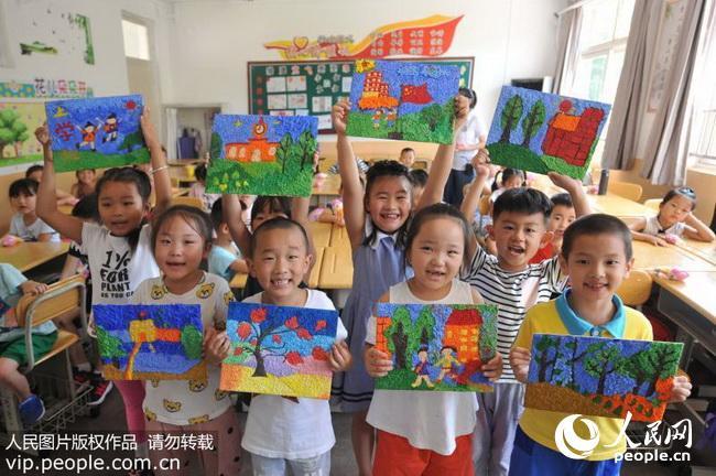 2018年8月30日,在山东青岛杭州路小学开学第一课上,一年级新生通过图片
