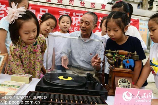 2018年9月23日,老党员在向小朋友介绍老式电唱机的使用方法.