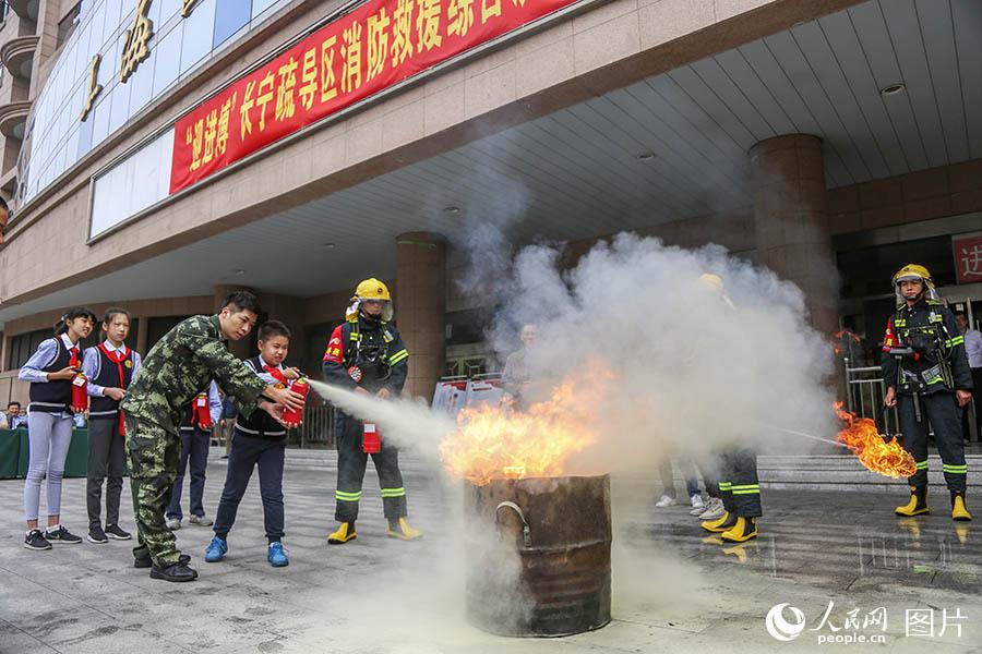 哈密路小学学生参与油桶灭火演练。