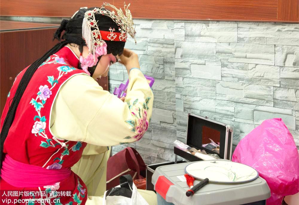 """2019年7月19日,江西省上饶市弋阳县东湖邓家村,演出后,孙晚霞在台边准备卸假发,孙晚霞从2005年开始学习弋阳腔,如今31岁的她已经是一个5岁孩子的妈妈。她说:""""在没有演出的时候,他们的日常训练也十分辛苦。虽然很累,但这已经成为一种习惯""""。"""