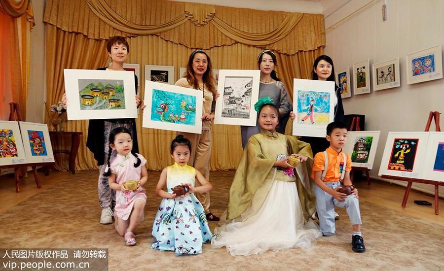 """萨基市历史博物馆画展现场,中国小画家表演""""儿童画创意紫砂秀""""。"""