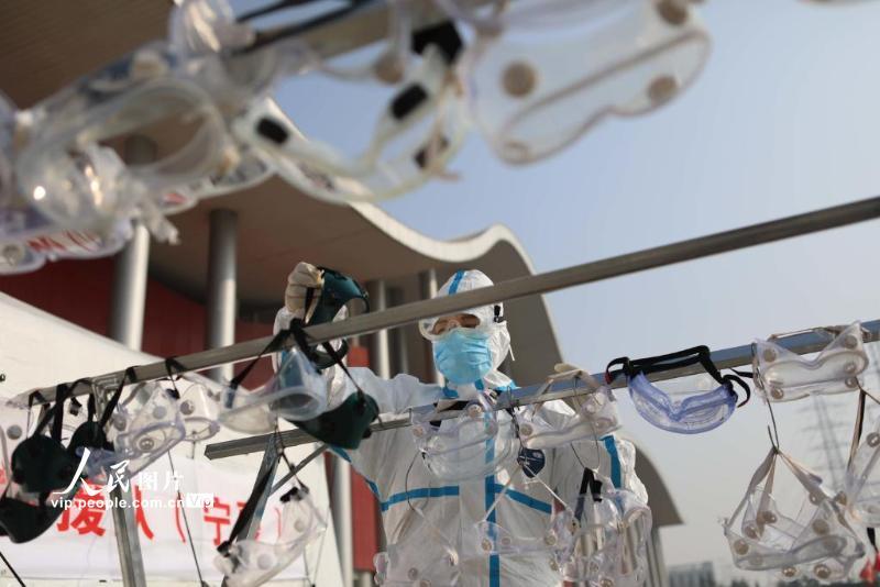 2月22日,武汉市武汉客厅方舱医院外,援鄂医疗队工作人员清洁护目镜。(李舸 人民图片)